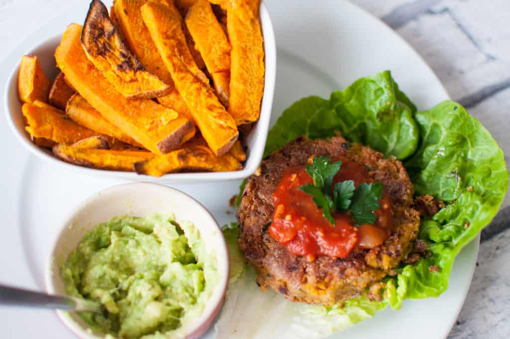 Clean eating falafel burger recipe made with only few ingredients. Top it with mashed avocado and homemade salsa! #vegan #cleaneating #nodairy #glutenfree