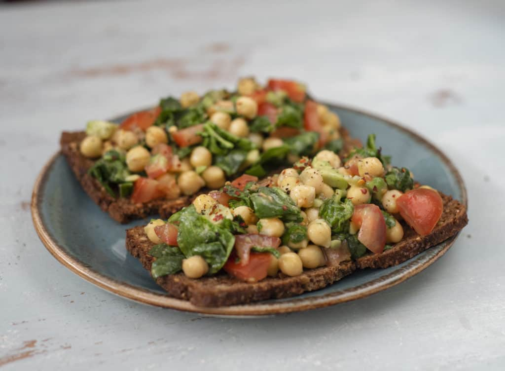 Healthy and super delicious Avocado Chickpea Tomato Toast recipe which is an easy fully plant based/vegan breakfast, snack or lunch for days when you can't be bothered to cook or it's too hot outside #vegan #avocadotoast #vegetarian #dairyfree