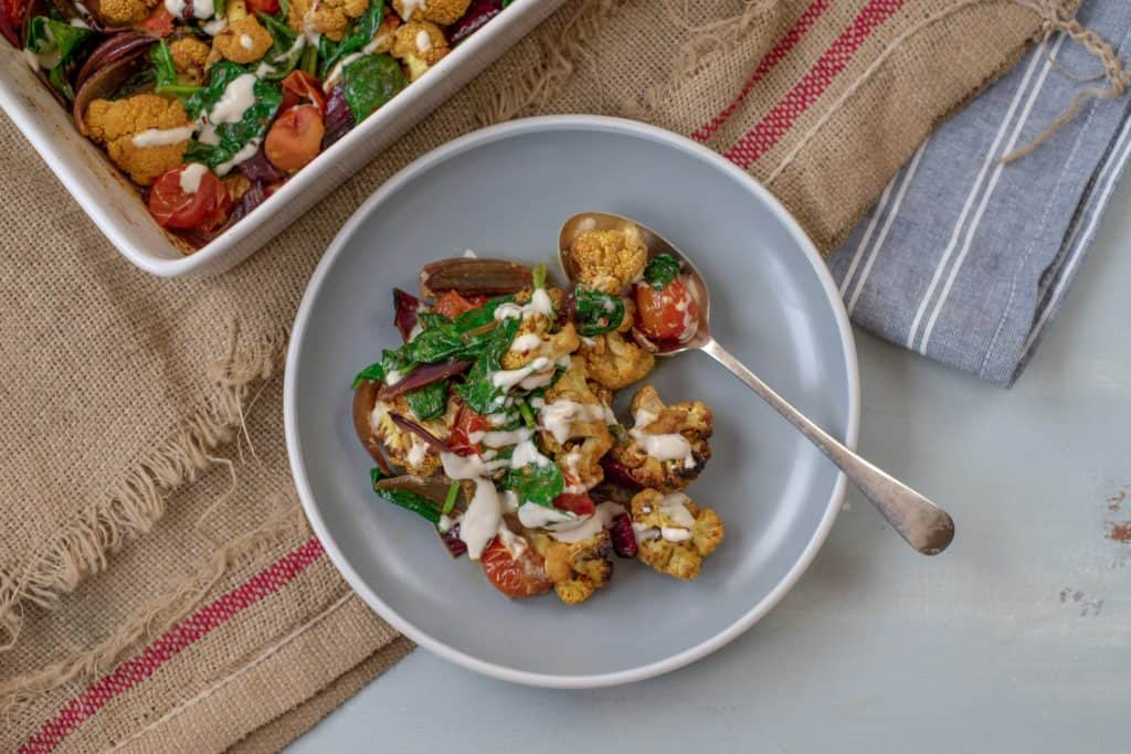 Absolutely delicious one-pot healthy cauliflower bake recipe served with lush tahini and yoghurt dressing. Super-satisfying while vegan, gluten & grain free!#veganrecipes #glutenfree #dairyfree #cauliflowerbake #healthyrecipes #cleanrecipes #cleaneating #easyrecipes