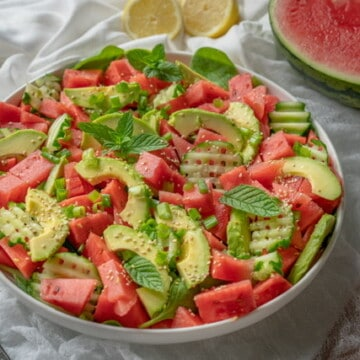 Delicious, quick and healthy watermelon salad with spinach, avocado, cucumber, spring onions and sesame seeds. Serve with freshly squeezed lemon juice! #easymeals #vegansalads #summerrecipes # eatwell #quickrecipes #homemade