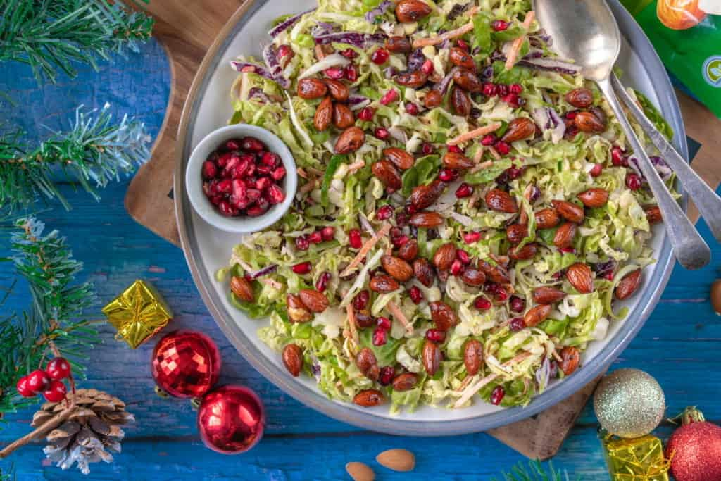 Healthy Brussels sprout slaw that comes with a creamy tahini dressing, spicy roasted almonds and pomegranates for a bit of sweetness. It's naturally vegan and gluten-free too! #veganchristmas #brusselssprouts #veganchristmas #christmasfood #healthychristmas #christmasfood #plantbased