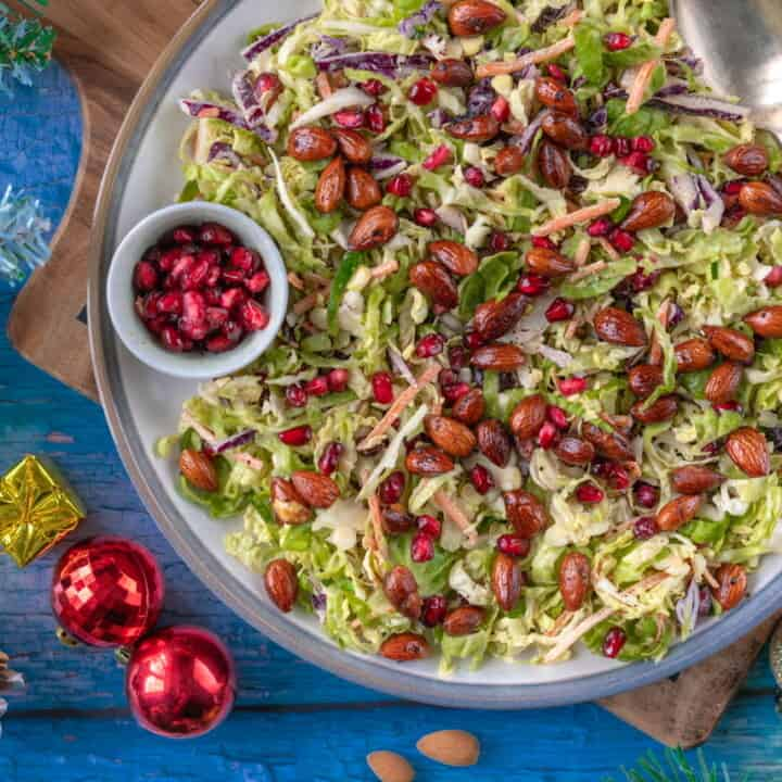 Healthy Brussels sprout slaw that comes with a creamy tahini dressing, spicy roasted almonds and pomegranates for a bit of sweetness. It's naturally vegan and gluten-free too.