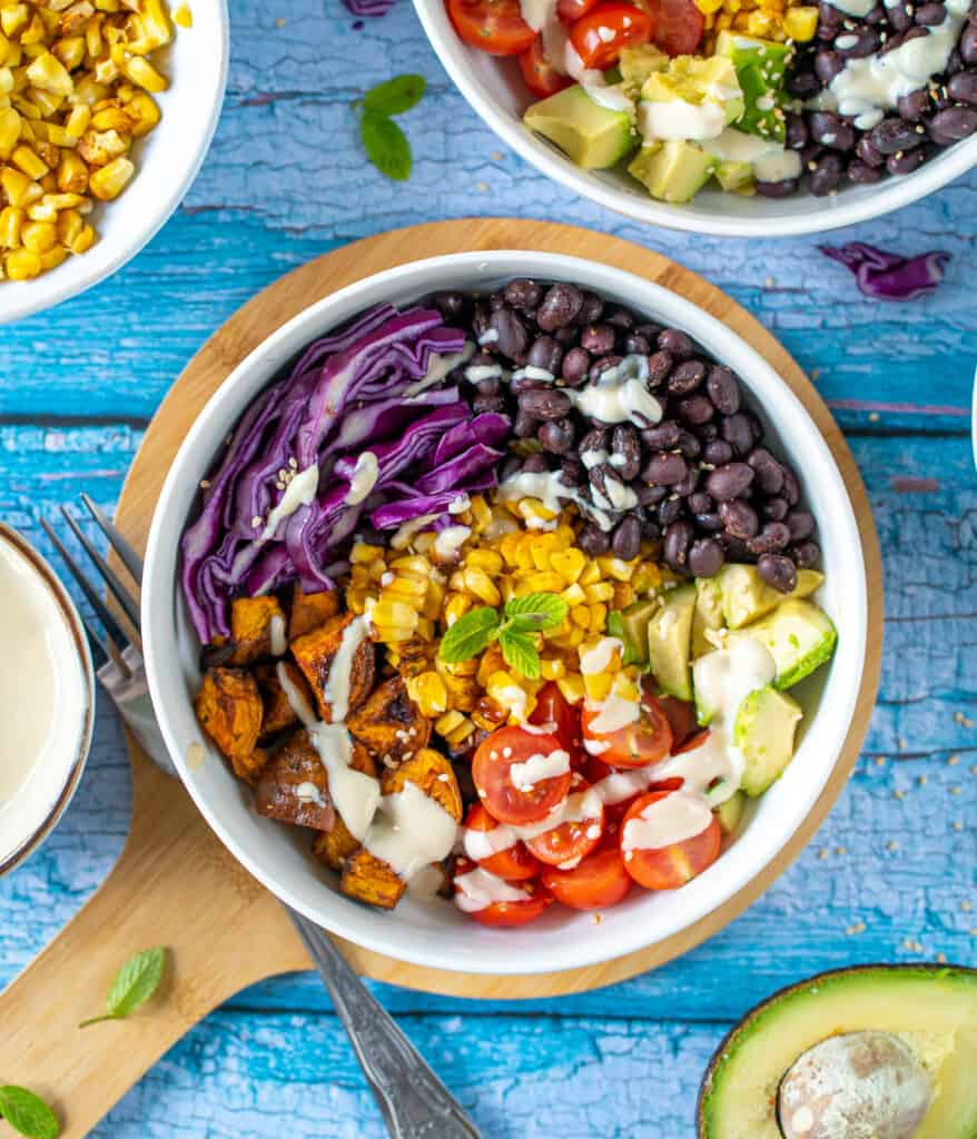 The best healthy Burrito Buddha Bowl packed with roasted sweet potatoes, smokey black beans, cherry tomatoes , creamy avocado and sweetcorn all drizzled with lush yoghurt and tahini dressing.