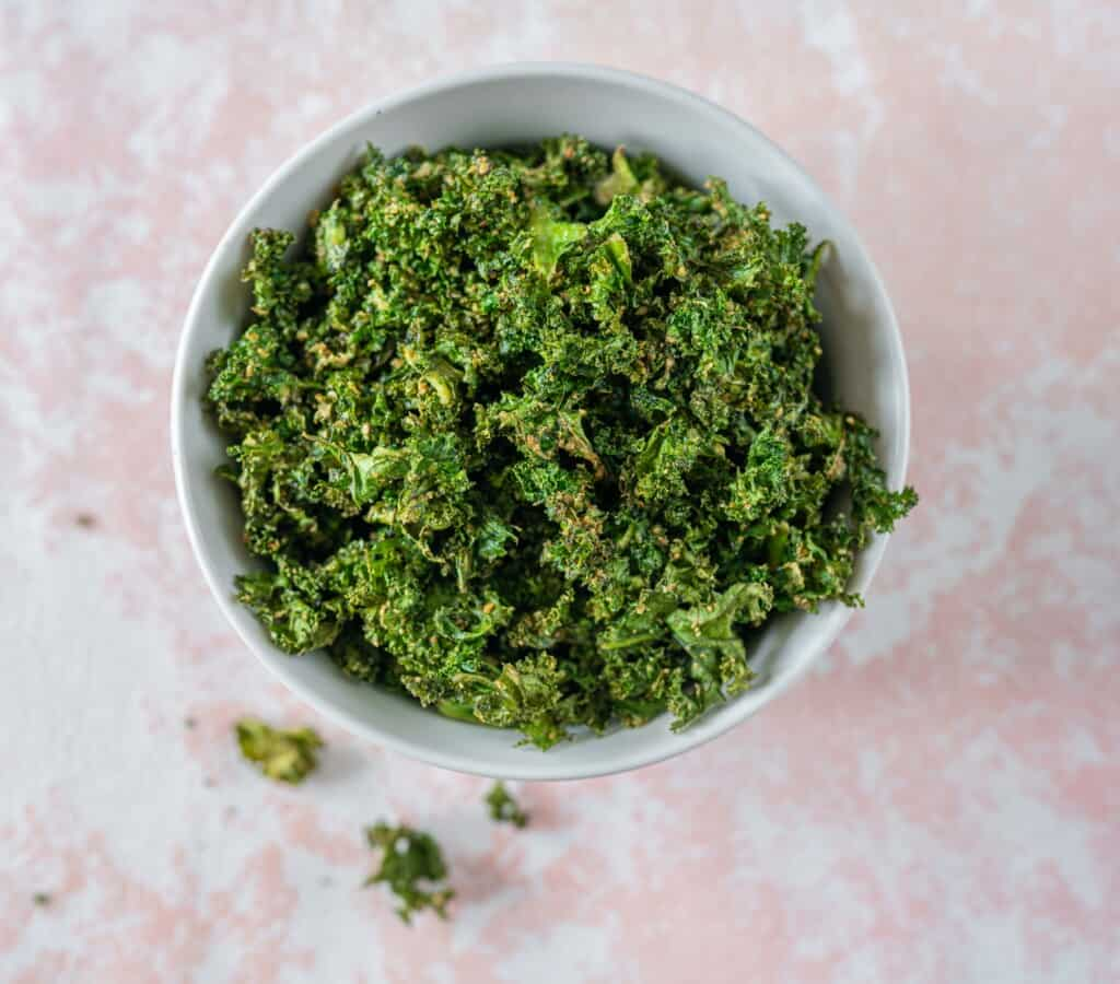 These cheesy kale crisps are super easy to make and a fantastic savoury snack loaded with fibre and nutrients. Vegan & Gluten-Free